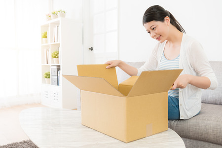 elegant young woman through online shopping websites buying personal goods and received the parcel at home looking at product feeling satisfaction.