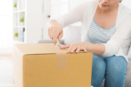 예쁜 여자 집에서 커터 나이프를 사용 하여 웃 고 개인 배달 소포 및주의 절단 테이프 깨진 상자를 피하십시오. 선택적 포커스 사진입니다.