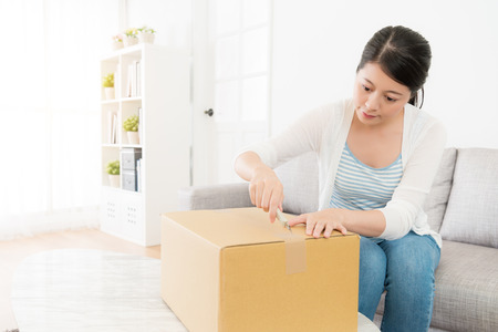 beauty sweet girl receives personal parcel at home and sitting on sofa couch using utility knife carefully cutting tape to open package .