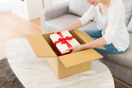 high angle view foto van glimlachende elegante vrouw ontvangen pakket thuis en zittend op de bank geopend vinden met geschenkdoos.