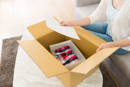 woman sitting on sofa at home opening personal online shopping parcel package and holding order list paper to confirm goods.