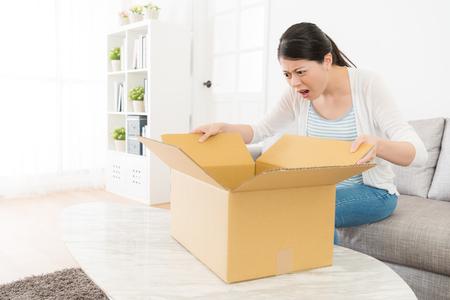 화가 젊은 아가씨 배달 패키지 그녀의 온라인 쇼핑 상품을 가지고 있지 않기 때문에 불행을 느끼는 그녀의 소포 상자를 찾고.