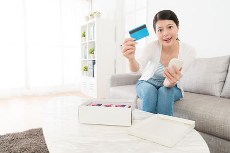 cheerful beauty woman showing credit card looking at camera when she using mobile smartphone online shopping and through e-commerce paying. Reklamní fotografie