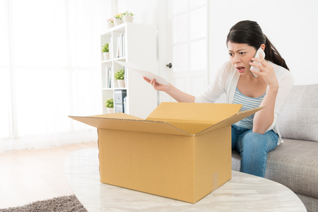 beautiful young woman received online shopping parcel opening box finding order goods is wrong feeling angry and using mobile cell phone calling for store center complaint. Stockfoto