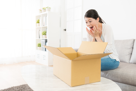 彼女は誕生日の贈り物を持っている小包ボックスを受け取ったときに興奮しているリビングルームのソファオープンパッケージに座っている驚きの