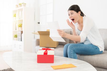 幸せなショックを受けた女性自宅個人宅配ボックスを開梱および文字コンテンツ検索を見てソファの上に座ってびっくり驚いた感じのニュースです