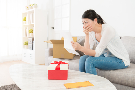 sadness unhappy woman sitting on sofa reading letter content crying when she opening cardboard parcel box getting birthday gift.