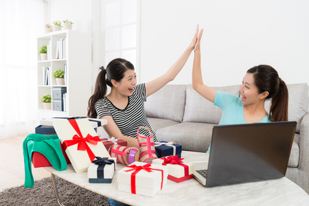 pretty happy women using computer online shopping at home and successful buying summer sale goods feeling cheerful looking each other giving clap. Stock Photo