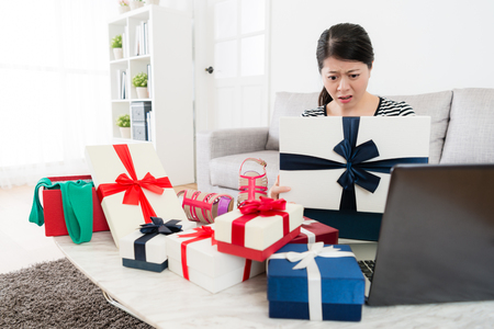 young sweet girl looking at gift box feeling confused when she using computer online shopping and received summer sale season present at home.