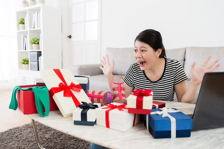 cheerful beautiful girl looking at many summer sale gift box feeling surprised and using mobile computer online shopping at home.