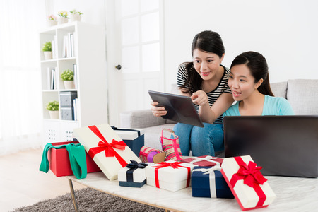 smiling attractive girls using mobile pad computer online shopping together and pointing screen to choosing summer sale goods at home.