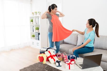 linda mulher segurando o vestido de verão novo deixa a irmã olhando e verificar se adequado e usando compras on-line de computador móvel em casa. Foto de archivo