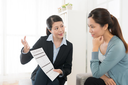 confident attractive business sales woman showing insurance case product for young girl at home and explaining scheme benefit. Foto de archivo