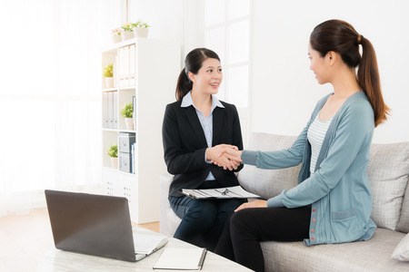 happy attractive insurance agent woman with beautiful young girl sitting on sofa couch handshakes when they finished deal.