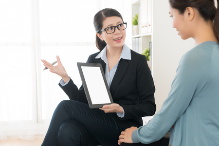 professional smiling insurance agent looking at her client talking discussing choos scheme and using mobile pad computer showing document. Stock Photo