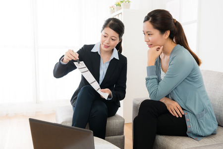 friendly pretty business worker woman holding document showing insurance plan for young investor and explaining best price.