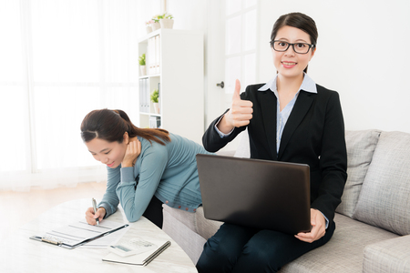 confident attractive insurance agent sitting on sofa couch face to camera and showing thumb up gesture when her customer signing deal in background.