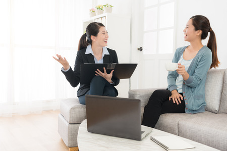 happy attractive lady sitting on sofa at home talking with her insurance advisor and discussing plan reached consensus feeling cheerful.