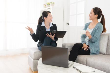 glückliche attraktive Dame, die zu Hause auf Sofa im Gespräch mit ihrem Versicherungsberater sitzt und Plan bespricht, erreichte Konsens, der fröhlich sich fühlt.