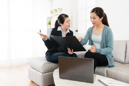 professional young business woman explaining insurance plan for client and beauty pretty girl pointing document asking problem. Archivio Fotografico