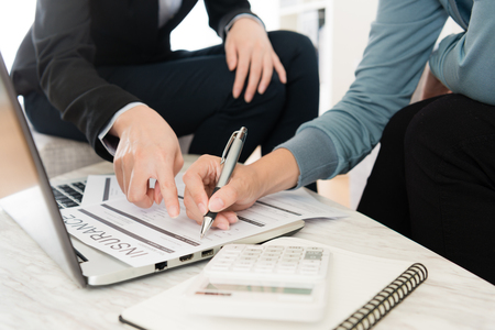 closeup photo of female customer fill in personal information on insurance document. Stock Photo