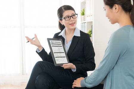 mulher bonita nova do conselheiro da gerência que usa o computador móvel da almofada que mostra o seguro de saúde e que explica o plano para convencer o negócio undersigned do comprador.