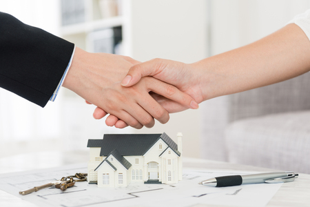 agent domu z powodzeniem sprzedaje koncepcję budynku - kobieta biznesu z inwestorem kupujący sfinalizował transakcję i uścisk dłoni.