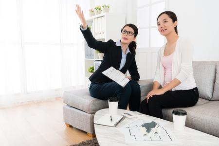 professionele jonge zakenagent met klantbezoek aan woningbouw en gebruik van blauwdrukdocument om geconstrueerd ontwerpplan uit te leggen.