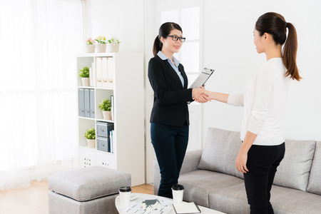 happy friendly business lady with her client handshake when they finished house deal and looking each other talking together.