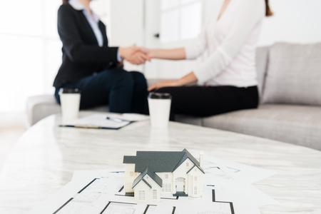 一緒に彼女のバイヤー契約終了ハンドシェイクを建物の場合が正常に販売顧問を家します。セレクティブ フォーカス写真。
