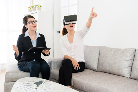 smiling friendly house agent explaining building design when her client using VR technology equipment viewing construction and pointing imitation image asking question.
