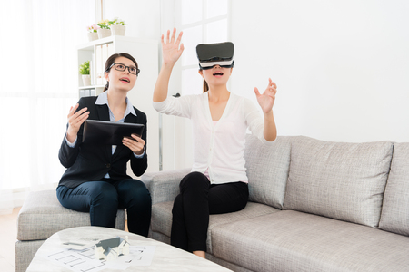 happy pretty female buyer wearing virtual reality technology device looking at 3D house simulation video and using hands touching screen viewing all building construction.