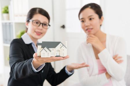 家モデルの議論を見てプロのアドバイザーの女性と投資家女性建築計画。セレクティブ フォーカス写真。