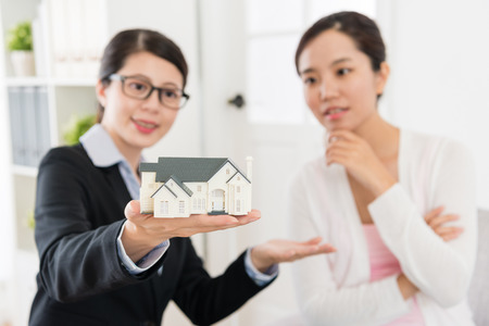 professional advisor woman and investor lady looking at house model discussing building construction design. selective focus photo. 스톡 콘텐츠