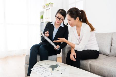 Gerente de ventas de la casa mostrando el documento del contrato de trato y la joven belleza preguntando el problema para discutir el mejor esquema para el plan de la casa.