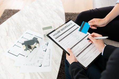 buyer woman using personal credit card e-commerce system buying house insurance to protecting personal building. high angle view photo.