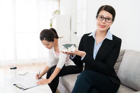 自信を持って若い家エージェント女性導入クライアントの最高の建物と彼女の買い手の署名者のバック グラウンドでのドキュメント。 写真素材