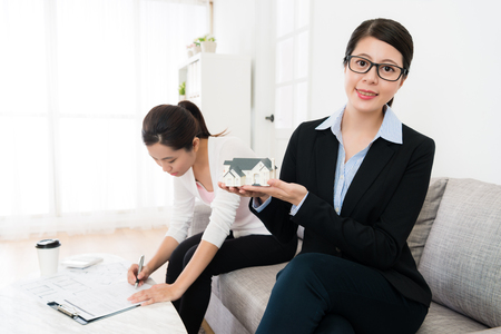 confident young house agent woman introduced best building for client and her buyer undersigned deal document in background.