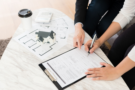 high angle view photo of buyer decision to buying new house and signing contract document finished deal at home with agent manager woman. Stock Photo