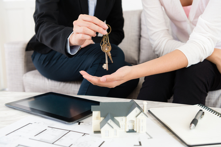closeup photo of saleswoman giving house key for customer when buyer signing deal contract and paying full amount money.
