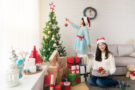 Asian mother sitting on the floor of the living room and daughter standing on the sofa decorate the Christmas tree together. merry Christmas and Happy Holidays.