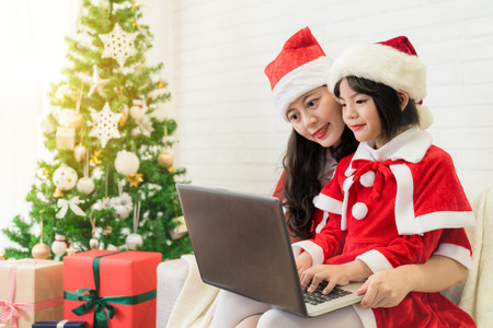 beautiful Asia Santa mother and cute little Asian kid using the computer to writing an email to Santa Claus to tell the expectation of Christmas gift at home.