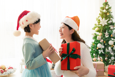 Cheerful Asian mom and her cute daughter girl exchanging gifts besides window. Parent and little child having fun near Christmas tree indoors. Morning Xmas. Portrait family close up.