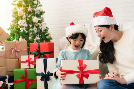cute Asian little daughter opens the Christmas gift box with her beautiful mother in the decoration living room at home.