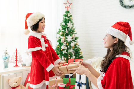 beautiful Asia mother gave her happy cute little Asian kid girl a present to play Christmas gift exchange in the living room at home. winter holiday vacation concept.