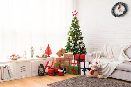 背景の明るいリビング ルームの下に贈り物を持つ完璧なクリスマス ツリー