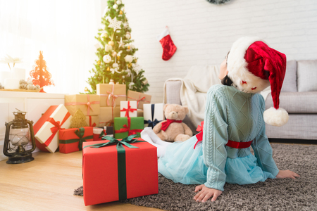 back view of a little cute girl sitting on the floor of living room with her big gift box face to decorate Christmas tree at home.