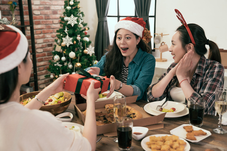 beautiful young girl feels surprised to receive a Christmas gift box from her friend. group of young friend holiday concept. Stockfoto