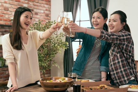 charming girls standing up celebrating together and hang up clink glass at home.