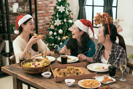Happy friends wearing Santa hats and sharing pizza with together in front of the Christmas tree
